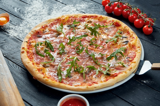 Pizza al forno con prosciutto crudo con salsa rossa e formaggio fuso su un tavolo di legno nero in una composizione con ingredienti. vista dall'alto