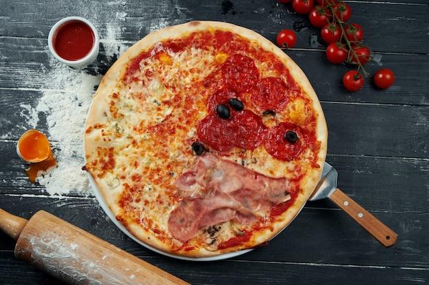 Pizza al forno con salame, prosciutto e pollo con salsa rossa e formaggio fuso su una superficie di legno nera in una composizione con ingredienti. vista dall'alto