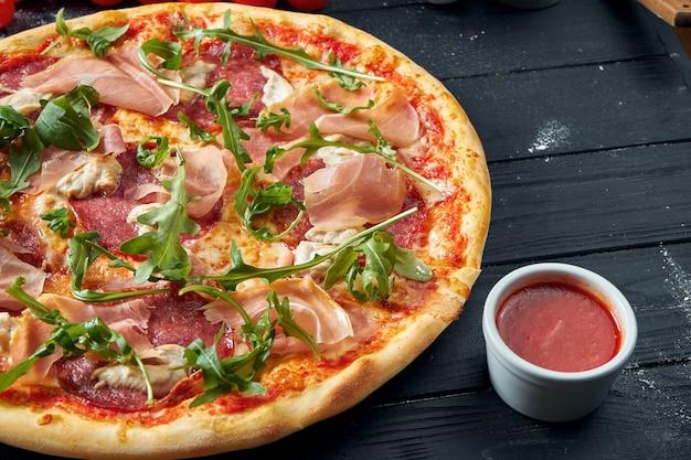 Pizza al forno con salame, prosciutto e pollo con salsa rossa e formaggio fuso su una tavola di legno nera in una composizione con ingredienti. vista dall'alto