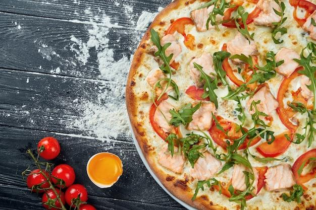 Pizza al forno con salmone, pomodori, formaggio fuso, besciamella e rucola su un tavolo di legno nero in una composizione con ingredienti. vista dall'alto. cucina italiana
