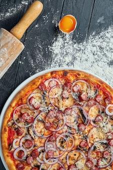 Pizza al forno con salsicce affumicate, cipolla rossa, funghi e formaggio fuso su un tavolo di legno nero in una composizione con ingredienti. vista dall'alto. cucina italiana