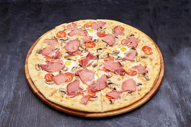 Pizza alla carbonara con pancetta e uova sul bellissimo tavolo grigio.