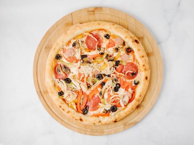 Pizza alle olive peperoni su un piatto di legno.