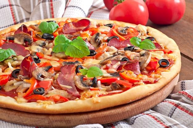 Pizza appetitosa con pollo, pomodori, peperoni e funghi