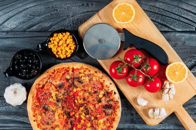 Pizza con aglio, pomodori, un limone, olive, mais e una taglierina per pizza vista dall'alto su uno sfondo di legno scuro