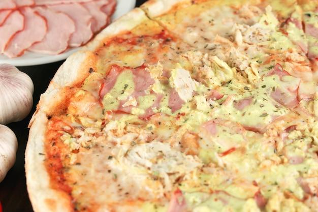 Pizza con alto vicino del pollo e del prosciutto