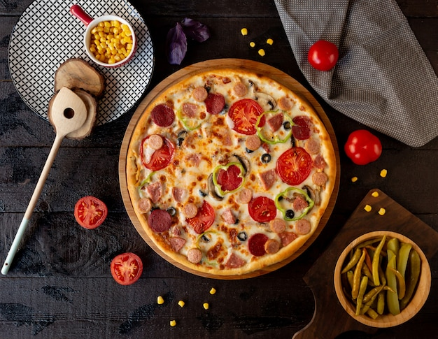 Pizza con fette di pomodoro e salame piccante.