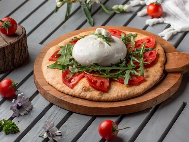 Pizza con fette di pomodoro, mozarella ed erbe aromatiche.