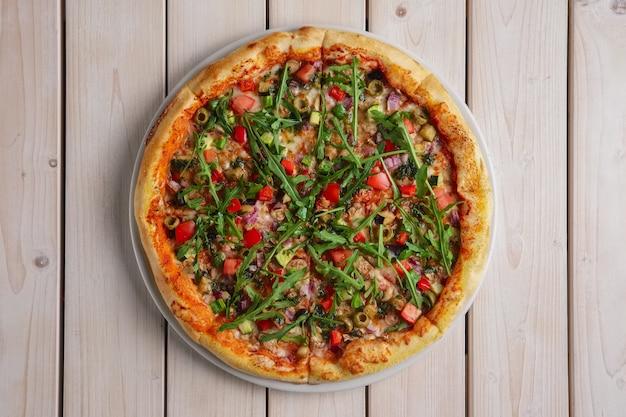 Pizza con funghi, zucchine, peperoni, cipolla e rucola