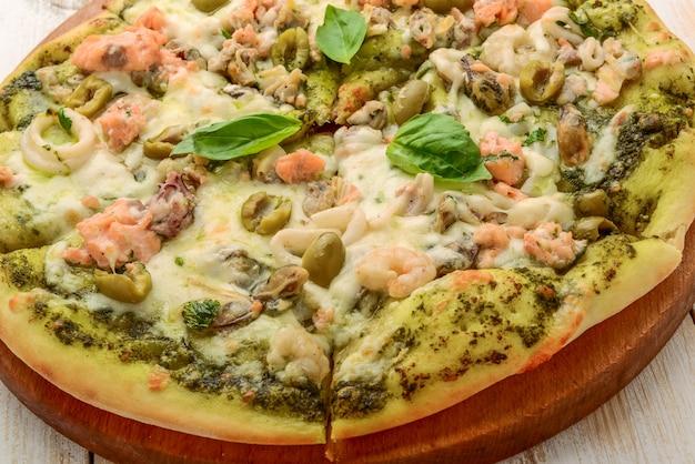 Pizza con gamberi, salmone e olive, pesto