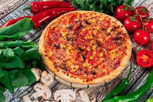 Pizza con i peperoni, i funghi, i pomodori, la pianta e le foglie di menta sul fondo leggero dello stucco, vista dell'angolo alto.