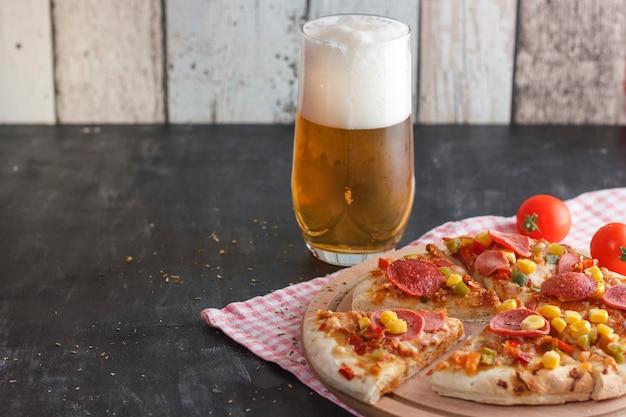 Pizza con mais, salsiccia, pomodori su una tavola di legno e birra leggera con schiuma in un bicchiere