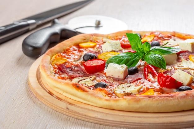 Pizza con mozzarella, prosciutto, pomodorini, olive nere