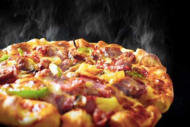 Pizza con pancetta e merguez prosciutto formaggio su sfondo nero isolato