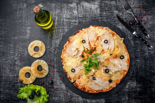 Pizza con pollo, ananas, formaggio e olive su pietra e uno sfondo nero graffiato in legno