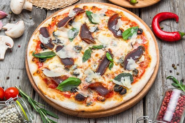 Pizza con pomodori, mozzarella, olive nere e basilico. pizza italiana deliziosa sul bordo di pizza in legno. vista da tavolo