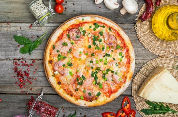 Pizza con pomodori, mozzarella, olive nere e basilico. pizza italiana deliziosa sul bordo di pizza in legno.
