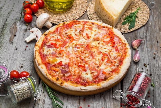 Pizza con pomodori, mozzarella, olive nere e basilico
