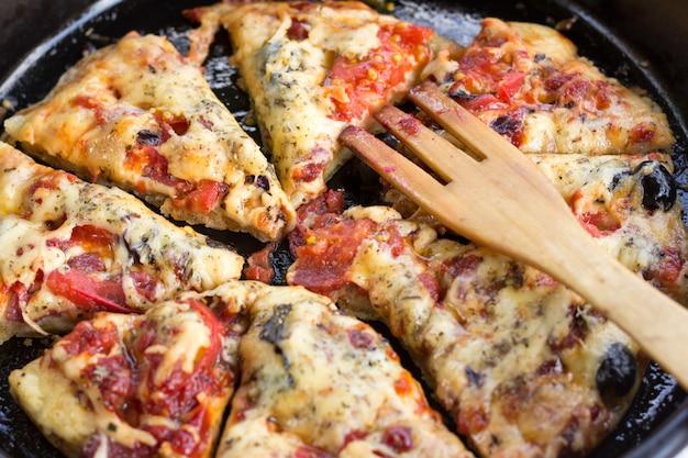 Pizza con pomodori, salsiccia e formaggio.