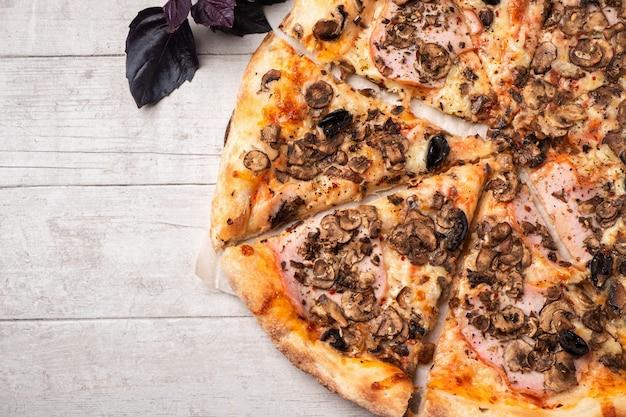 Pizza con prosciutto e funghi su un tavolo di legno bianco