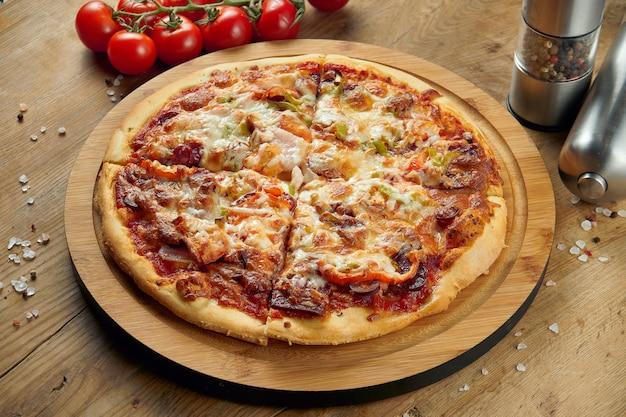 Pizza con prosciutto, formaggio, pomodorini, rucola sul vassoio di legno. avvicinamento. cucina italiana