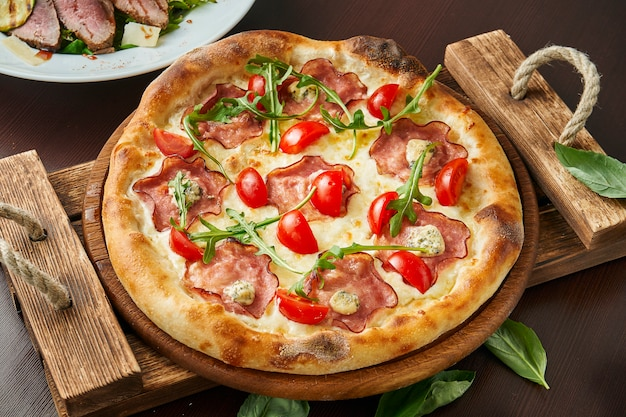 Pizza con prosciutto, formaggio, pomodorini, rucola sul vassoio di legno.