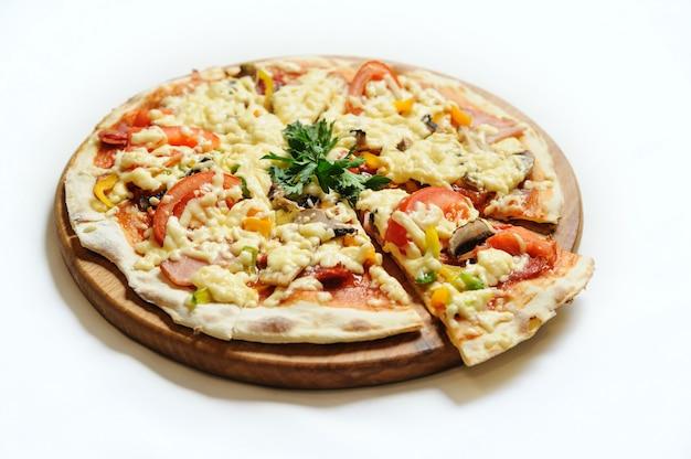 Pizza con prosciutto, funghi e pomodori.