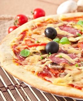 Pizza con salame, pomodori e funghi