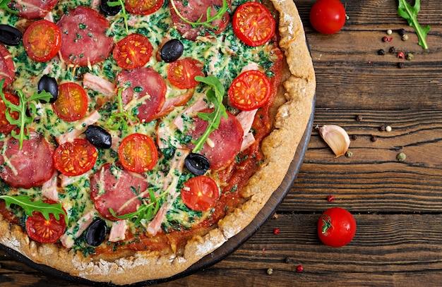 Pizza con salame, pomodori, olive e formaggio su un impasto con farina integrale. cibo italiano. vista dall'alto. disteso.