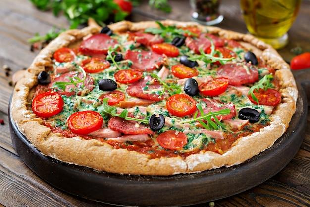 Pizza con salame, pomodori, olive e formaggio su un impasto con farina integrale. cibo italiano.