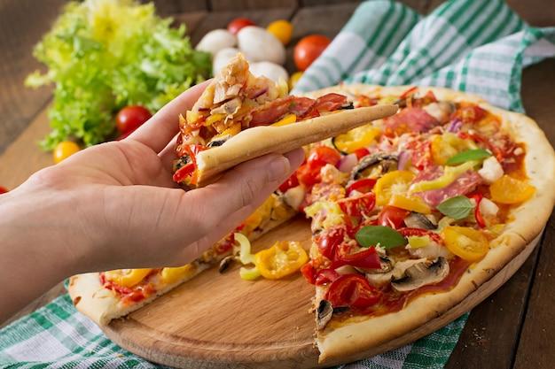 Pizza con salame, pomodoro, formaggio e funghi