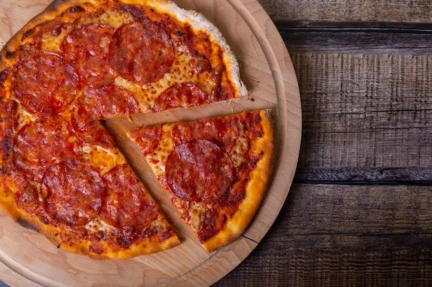 Pizza con salsiccia chorizo su una tavola di legno. pizza intera, tagliata un pezzo. primo piano, vista dall'alto, posto per il testo.