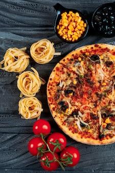 Pizza con spaghetti, pomodori, olive, mais close-up su uno sfondo blu scuro