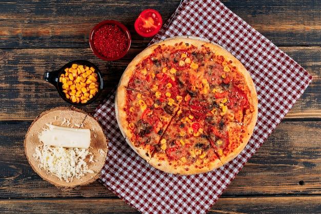 Pizza con una fetta di pomodoro, una barra di spezie e mais, formaggio sfuso su legno scuro e sfondo di panno picnic, primo piano.