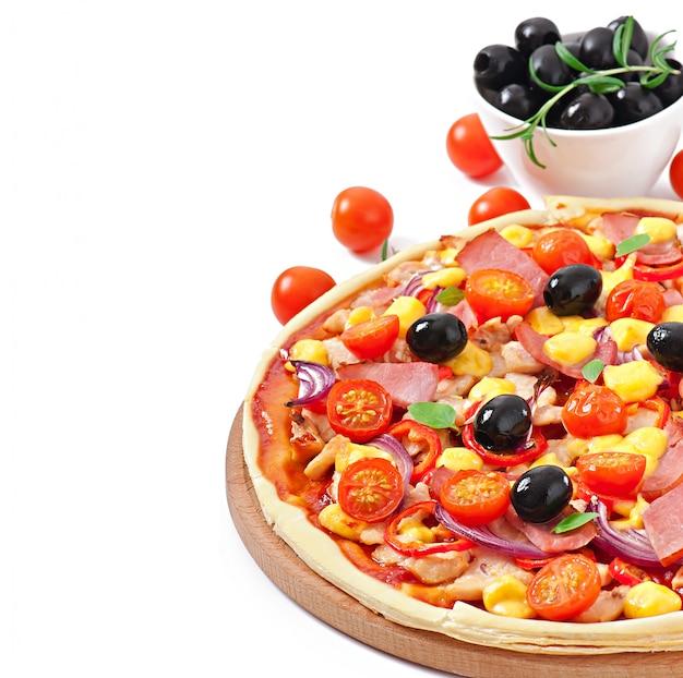 Pizza con verdure, pollo, prosciutto e olive isolati su bianco