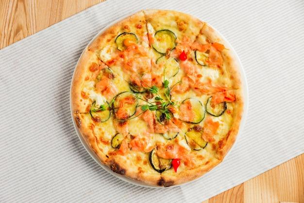 Pizza con zucchine, pesce rosso e formaggio, su un piatto bianco, vista dall'alto