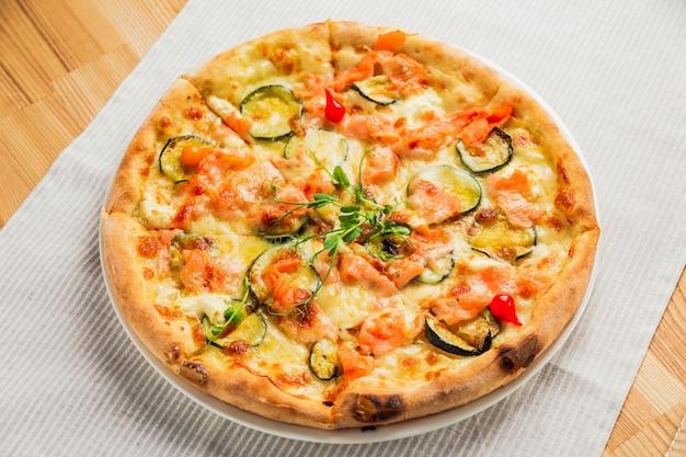 Pizza con zucchine, pesce rosso e formaggio, su un piatto bianco