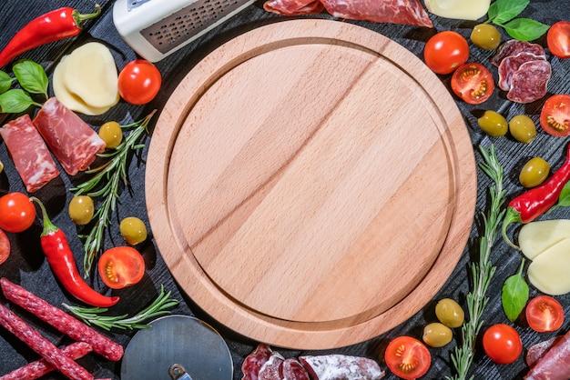 Pizza cruda ingredienti sul tabellone con copia spazio al centro.