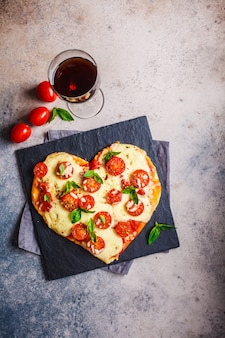 Pizza cuore con mozzarella e pomodori su ardesia con vino