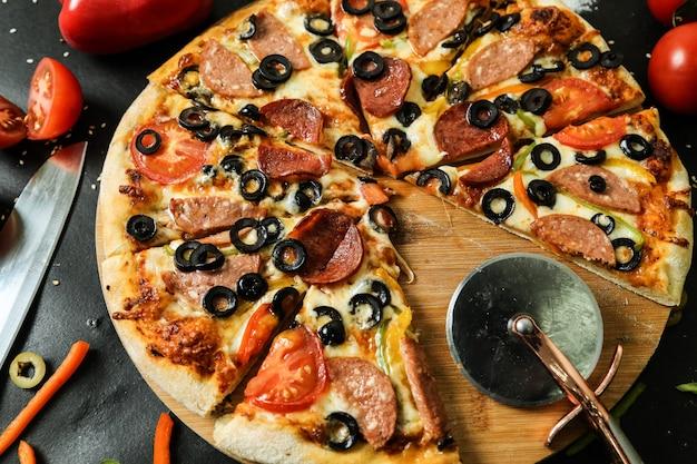 Pizza del salame di vista laterale sul supporto con le olive e il peperone dolce dei pomodori del coltello sulla tavola nera