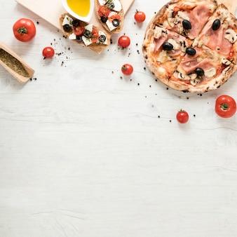 Pizza deliziosa con ingrediente sano su fondo di legno bianco