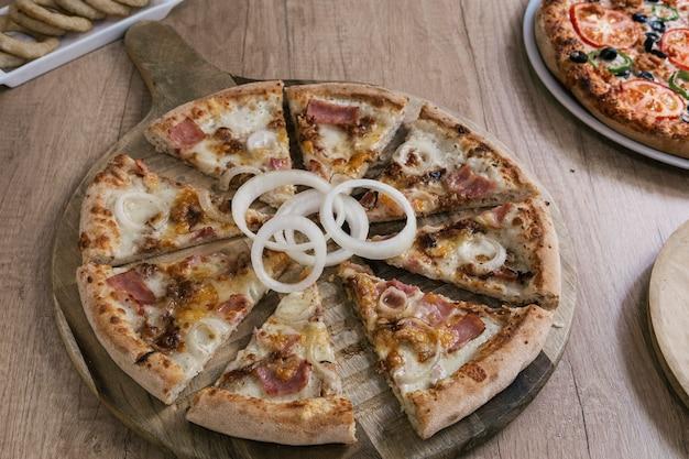 Pizza deliziosa del bacon, del formaggio fuso e della cipolla sul bordo di legno.