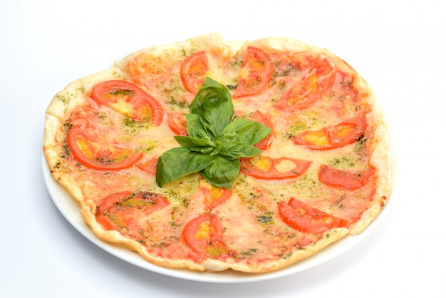 Pizza della margarita con i pomodori e basilico su bianco