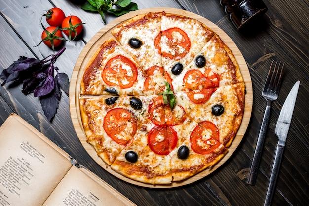 Pizza della margarita con la vista superiore del basilico verde oliva del pomodoro