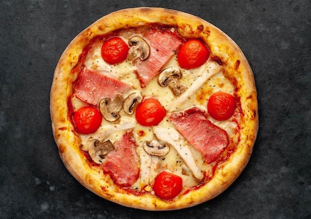 Pizza di carne con formaggio, pollo, prosciutto, funghi champion, pomodori