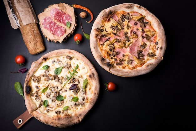 Pizza di funghi e salumi con ingredienti disposti su una superficie nera
