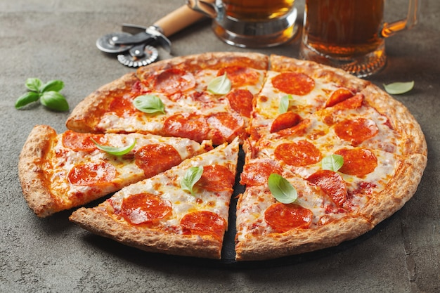 Pizza di peperoni saporita con basilico e bicchiere di birra su fondo di cemento marrone.