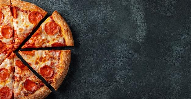 Pizza di peperoni saporita su uno sfondo di cemento nero.