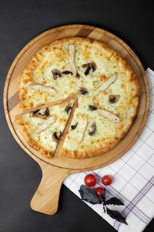 Pizza di pollo con funghi e pomodori sul tavolo