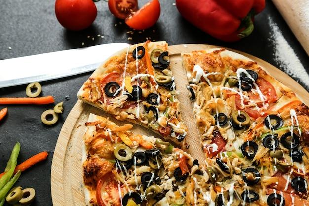 Pizza di pollo vista dall'alto con pomodori peperoni e olive su un vassoio